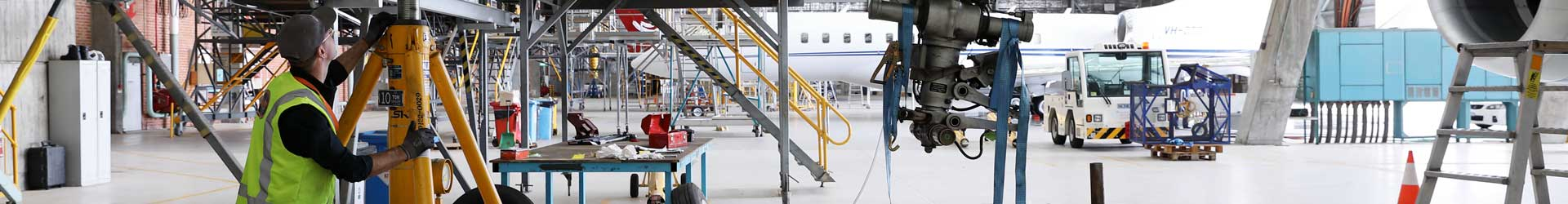 Aviation engineer assisting with aircraft maintenance in a hangar