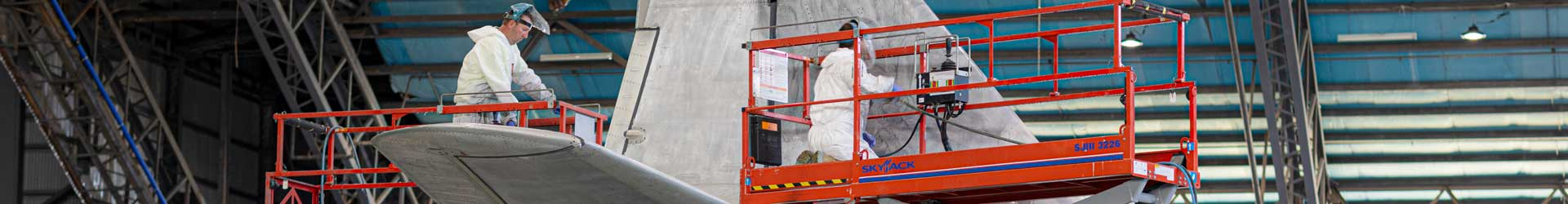 Aircraft refinishers on mobile scaffold painting an aircraft
