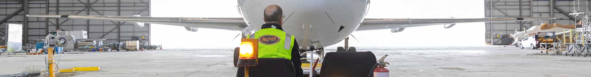 Aviat Global engineer towing a jet aircraft to the hangar